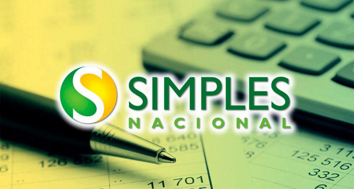 """O fundo da imagem é composto por uma caneta, uma calculador e folhas contendo cálculo. No primeiro plano, está a logo do """"Simples Nacional""""."""